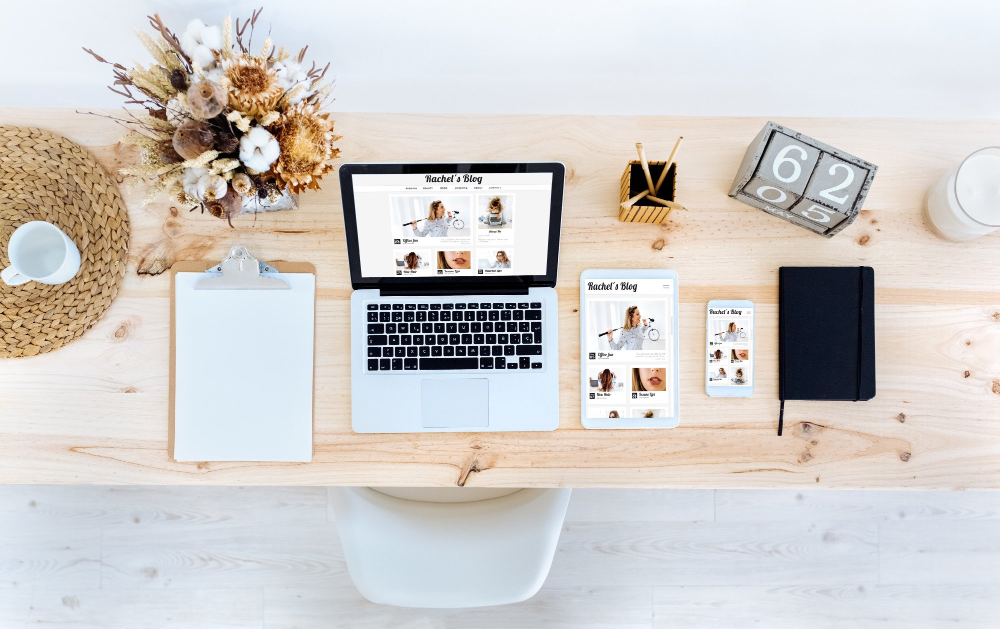 Laptop, tablet and smartphone on a desktop showing influencer girl blog.