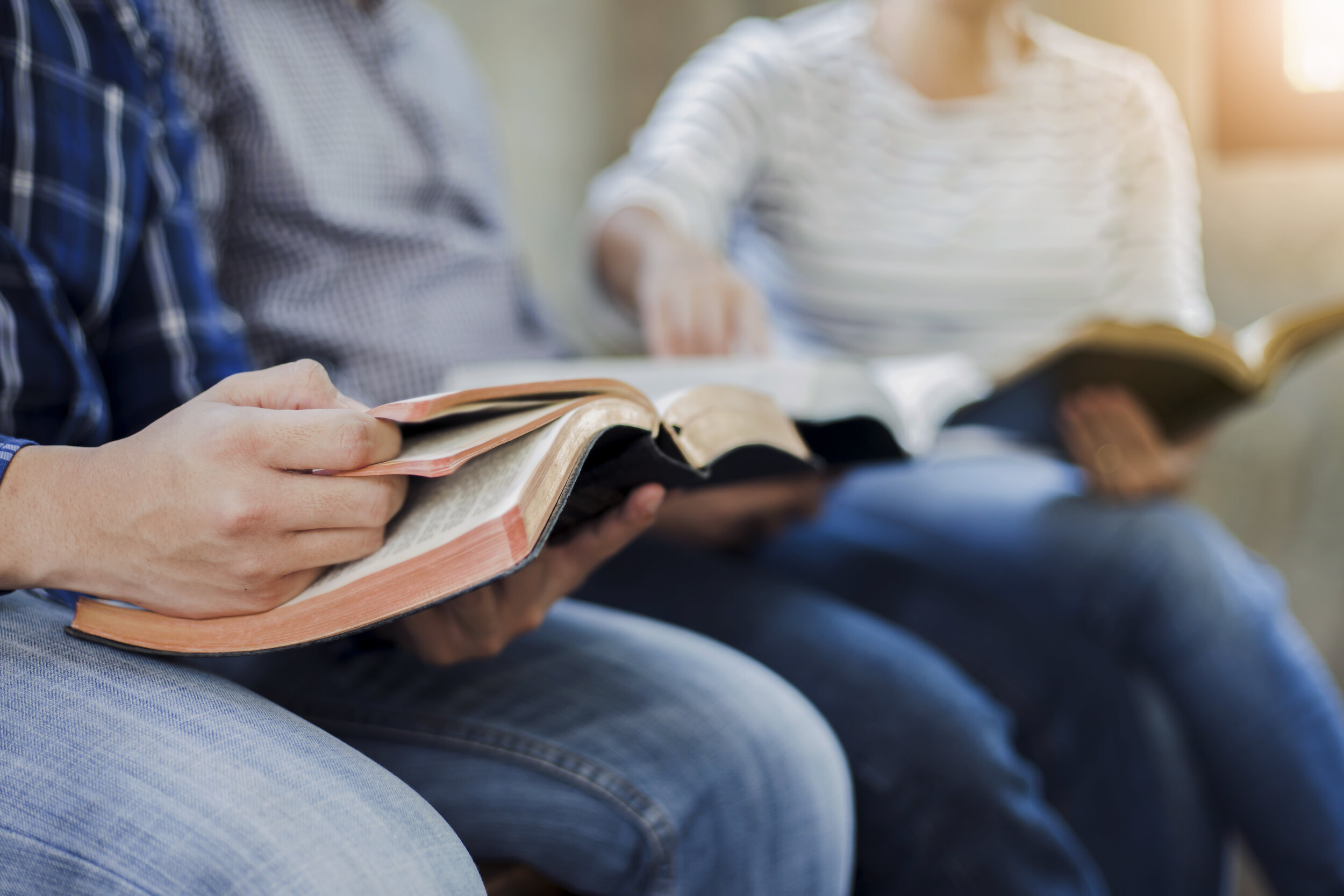 Christian friends group reading and study bible together in home or Sunday school at church with window light